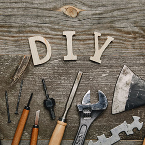 """Wooden table with wooden letters """"DIY"""" and tools on the table"""